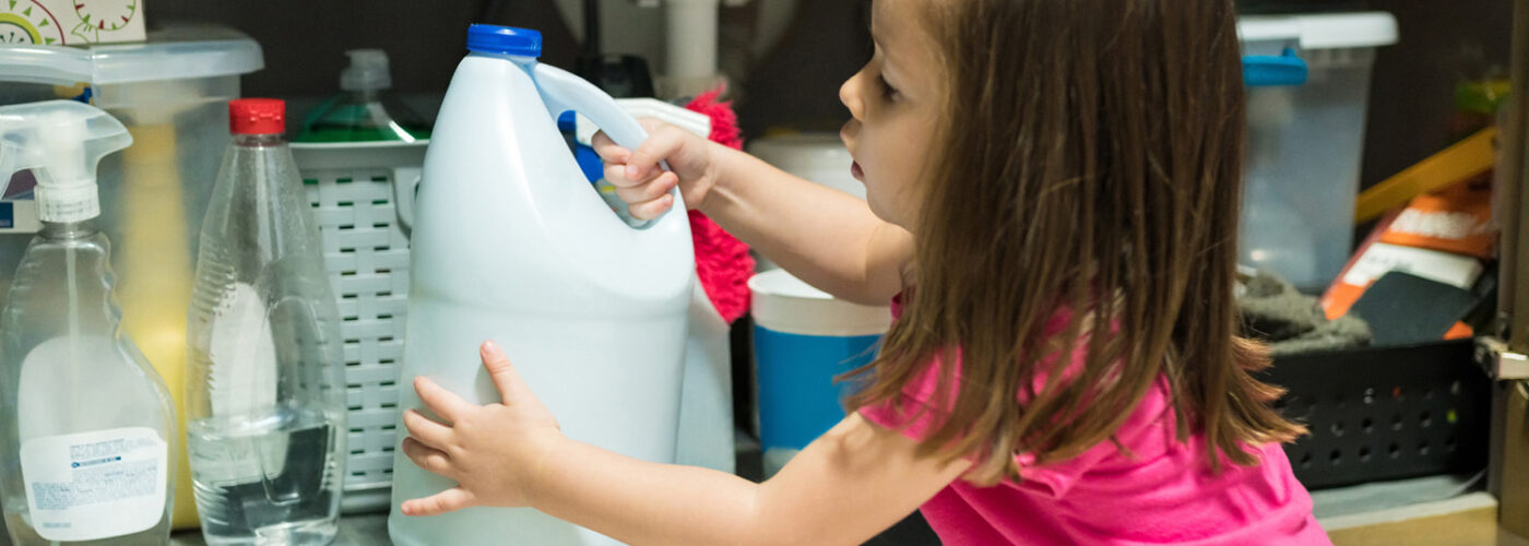 Young child grabbing chemical container